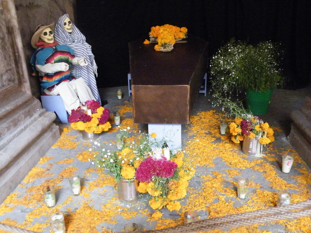 Skeleton figures watching over a marigold-decorated coffin